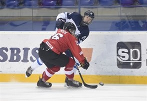 POPRAD, SLOVAKIA - APRIL 15: Finland's Teemu Engberg #18 passes the puck past Switzerland's Nico Gross #26 during preliminary round action at the 2017 IIHF Ice Hockey U18 World Championship. (Photo by Andrea Cardin/HHOF-IIHF Images)